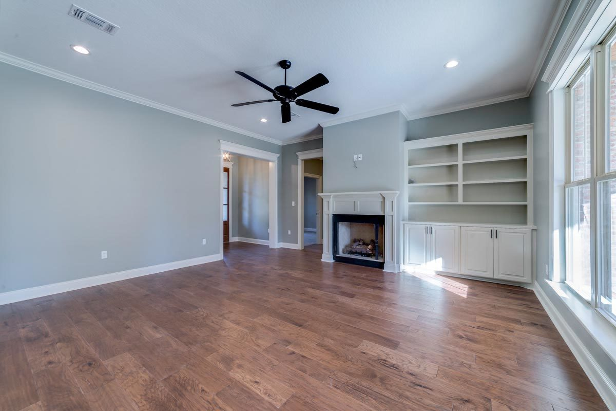 The living room has a wrought iron fan, a fireplace, and a white built-in cabinet.