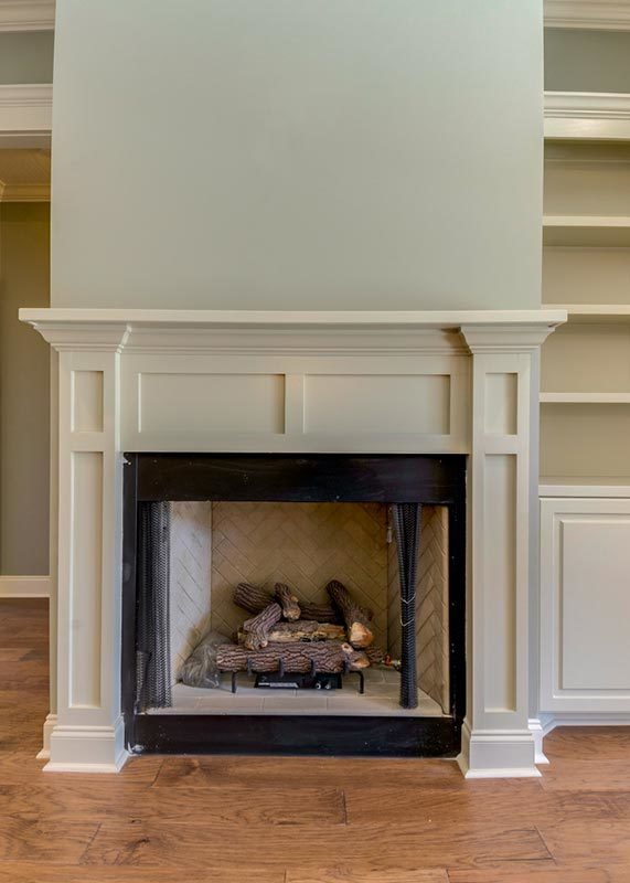 A closer look at the fireplace with herringbone firebox and wainscoted mantel.