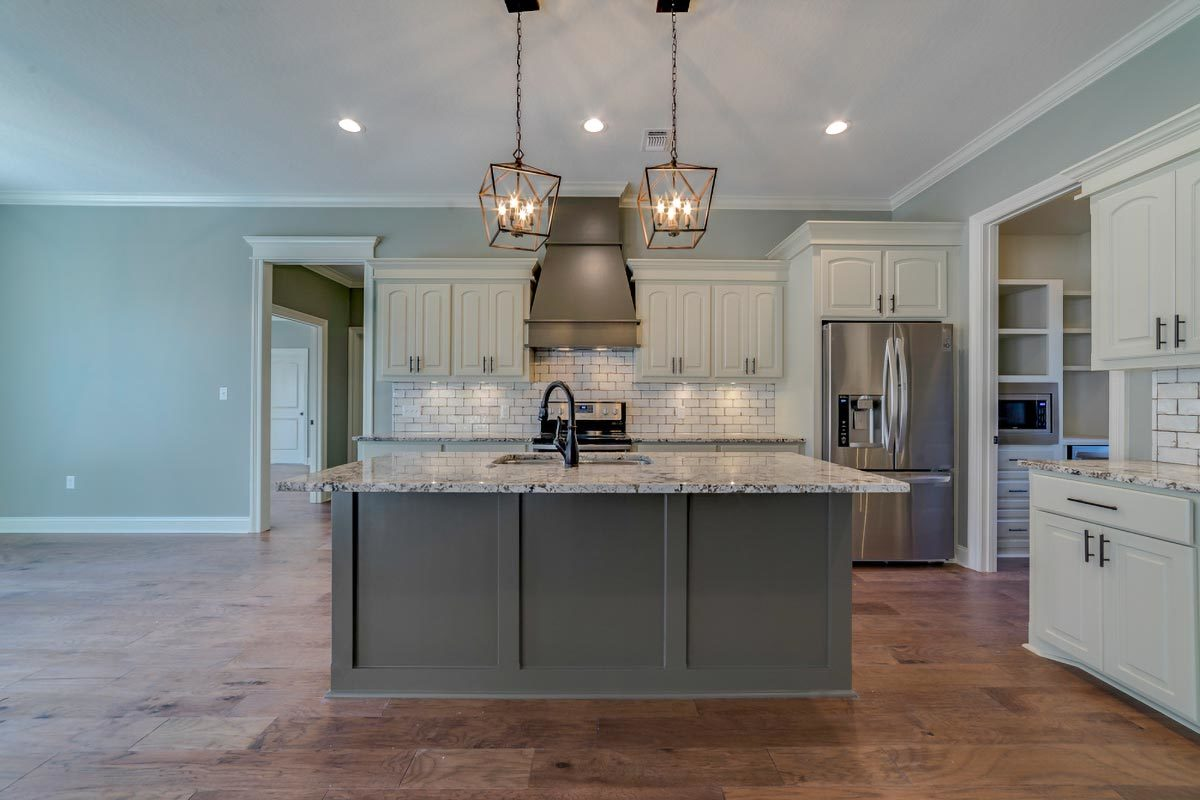 Kitchen with white cabinetry, granite countertops, and a center island.