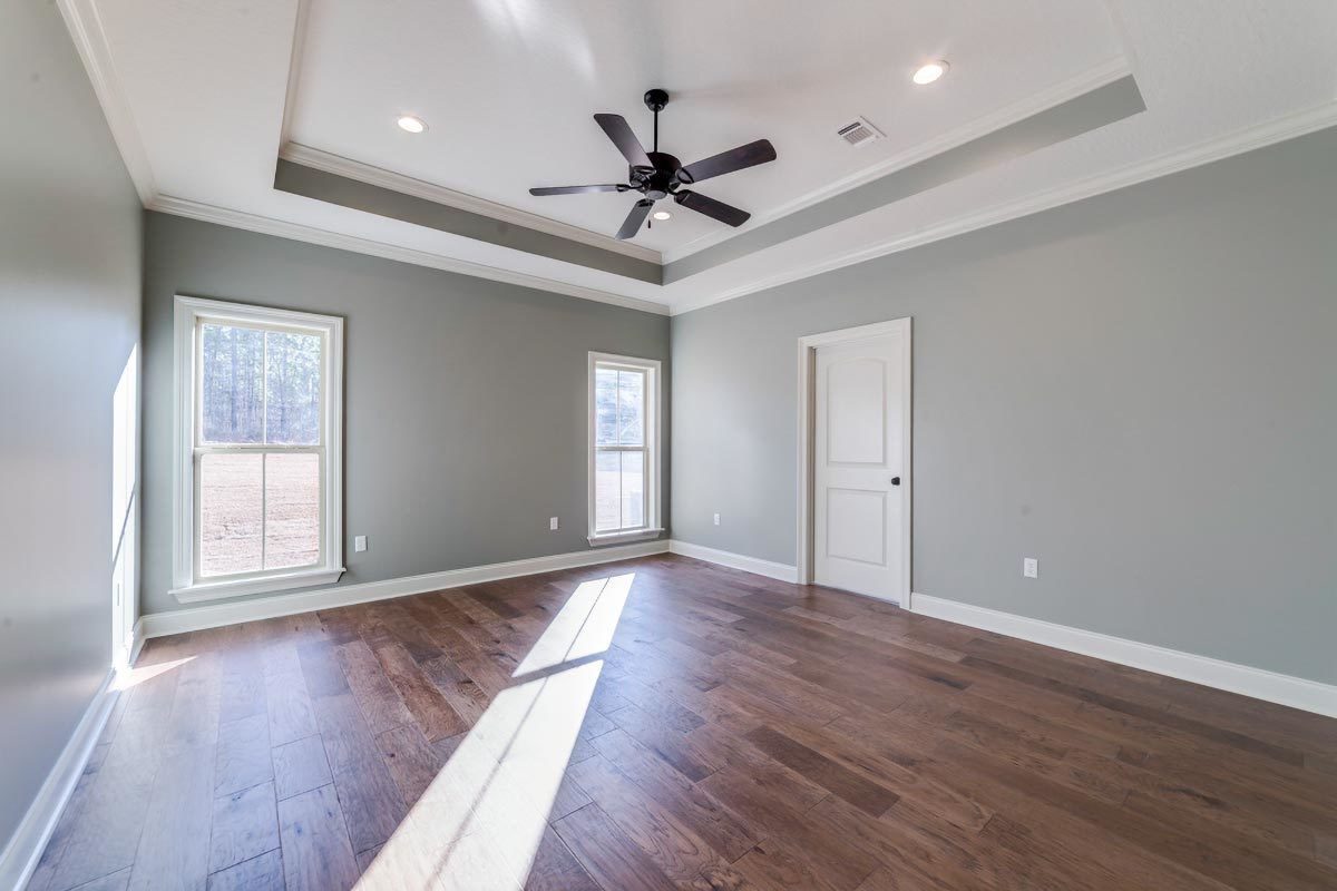 This is the primary bedroom with gray walls, hardwood flooring, and a tray ceiling mounted with a wrought iron fan.