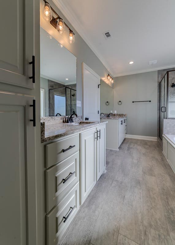 The primary bathroom offers double vanities paired with frameless mirrors.