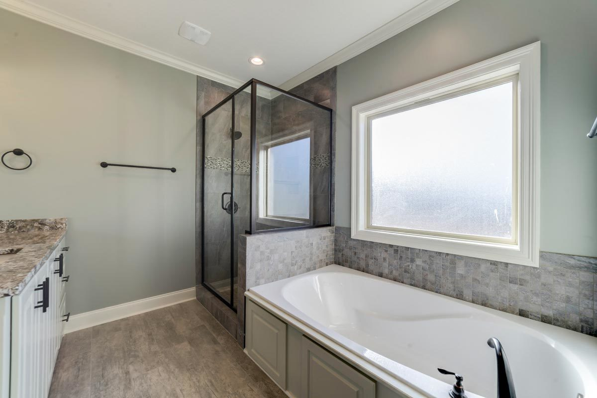Walk-in shower and deep soaking tub complete the primary bathroom.