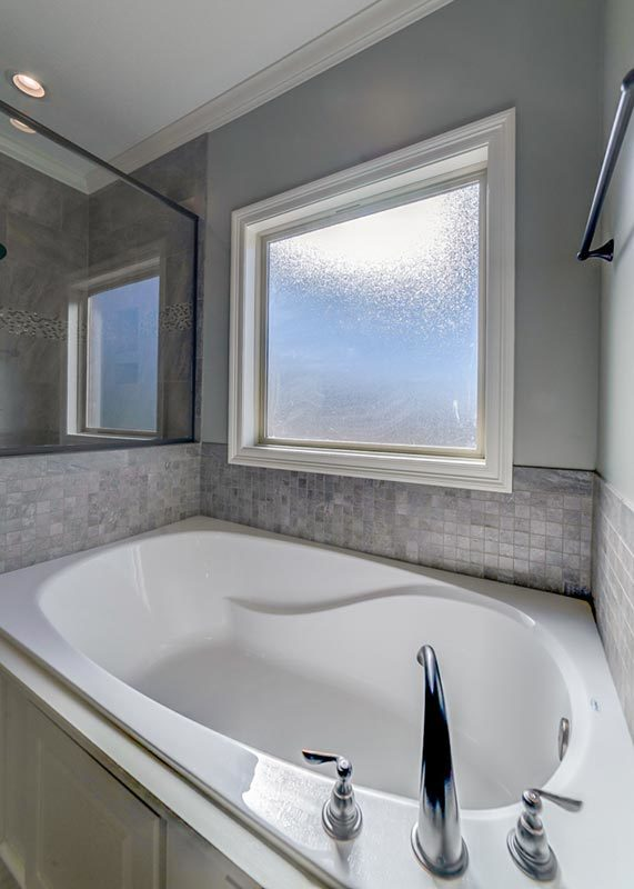 A closer look at the drop-in bathtub placed under the frosted glass window.