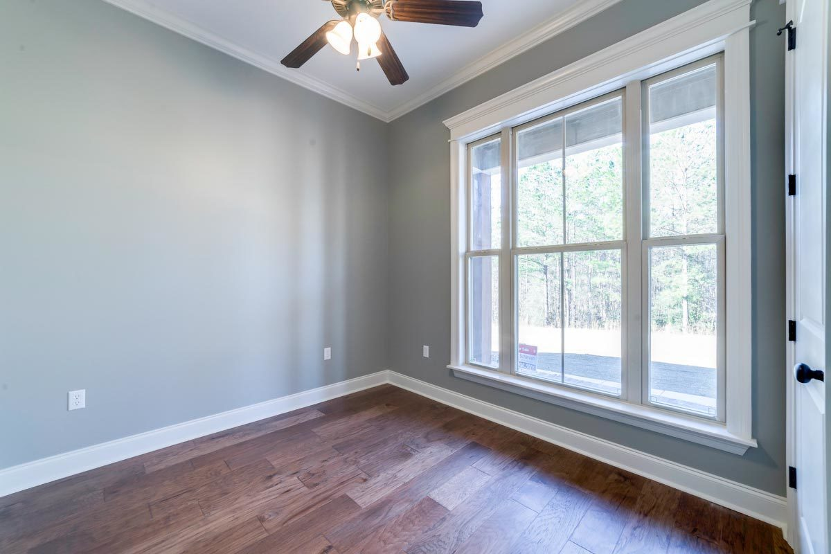 Another bedroom with gray walls and a large window that floods the space with natural lighting.