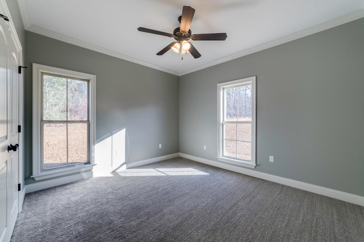 This bedroom has carpet flooring, gray walls, and a regular white ceiling.