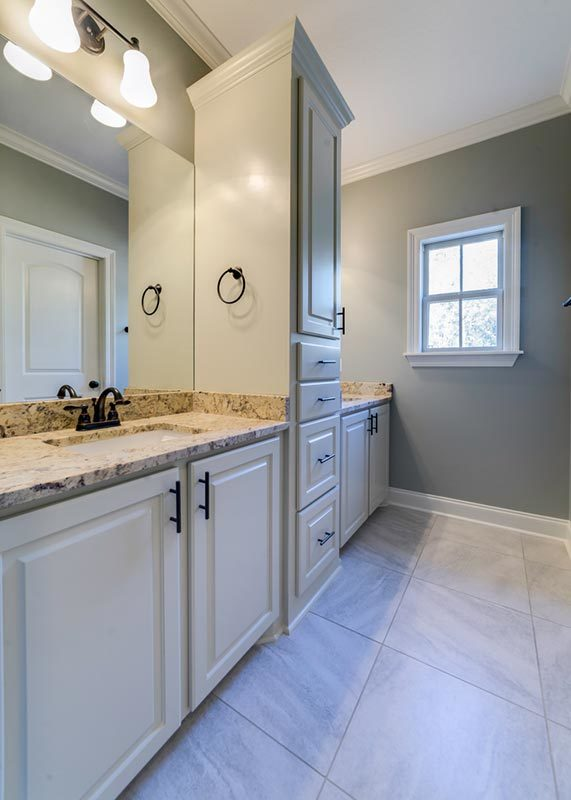 Bathroom with two vanities separated by a tall cabinet.