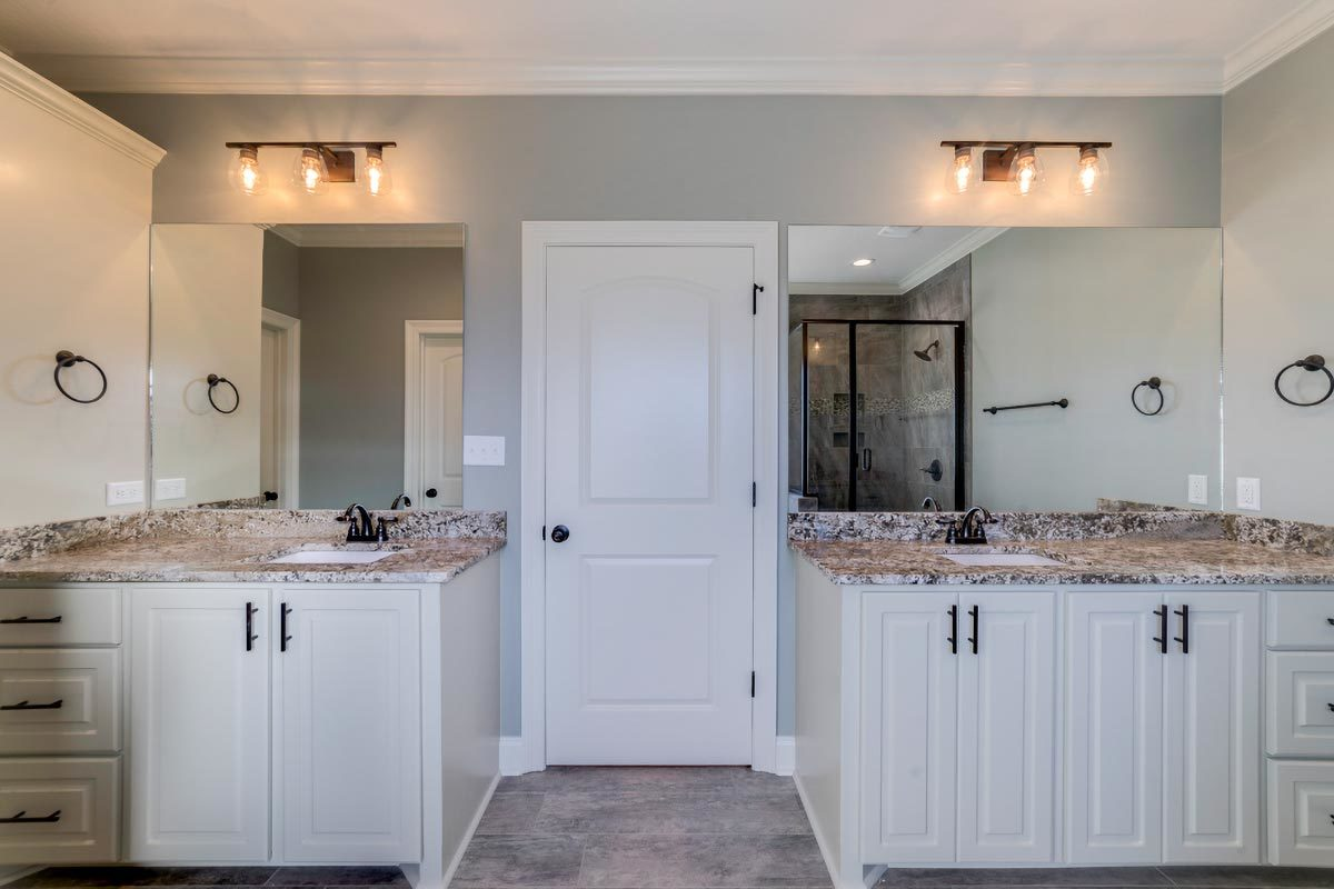 Primary bathroom with double vanities well-lit by warm glass sconces.