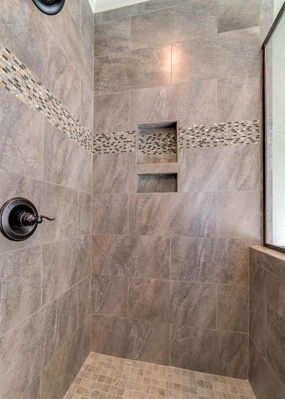 The walk-in shower includes inset shelves, wrought iron fixtures, and tiled walls.