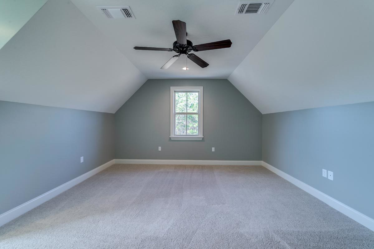 Bonus room with carpet flooring and a coved ceiling mounted with a wrought iron fan.