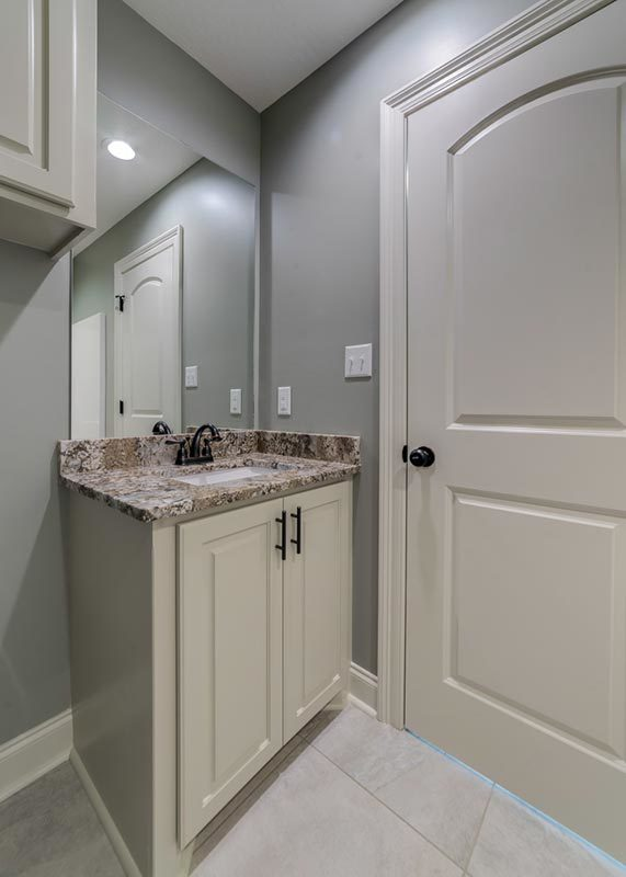 Bonus bath with a sink vanity, frameless mirror, and overhang cabinet.