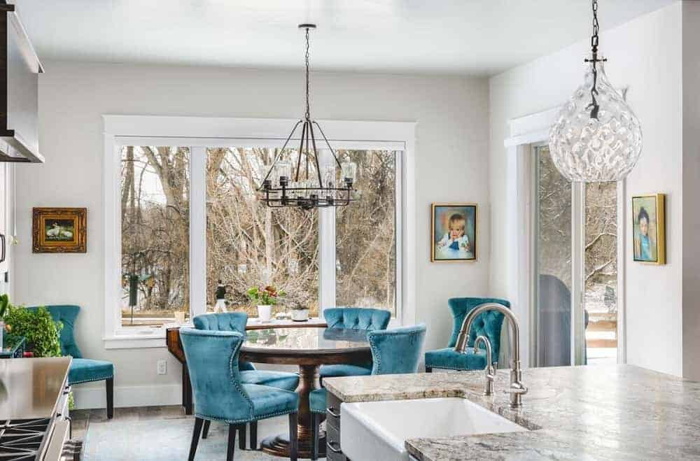 This is a simple and informal mountain chalet-style dining area by the kitchen that has a round wooden dining table surrounded by blue cushioned chairs complemented by the chandelier and the glass windows.
