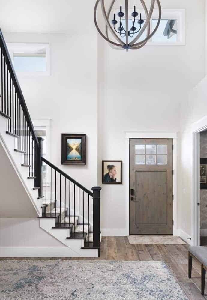 This is a mountain chalet-style foyer with a simple wooden door that opens to a bright beige and tall-ceilinged area that has hardwood flooring and large chandelier hanging by the stairs.