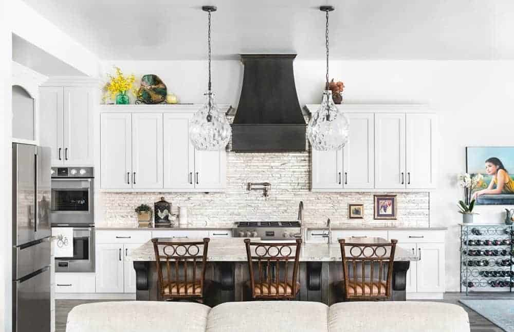 This is a full view of the mountain chalet-style kitchen that has consistent white cabinetry that matches the walls and ceiling as well as the kitchen island topped with glass pendant lights. These are then complemented by the stone textured backsplash.