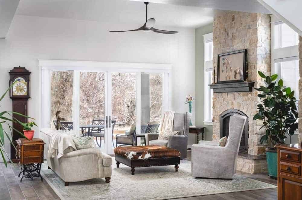 This is a mountain chalet-style living room that has a large stone textured wall that houses the fireplace across from the sofa set that matches the bright beige walls and ceiling brightened by the glass walls on the far side.