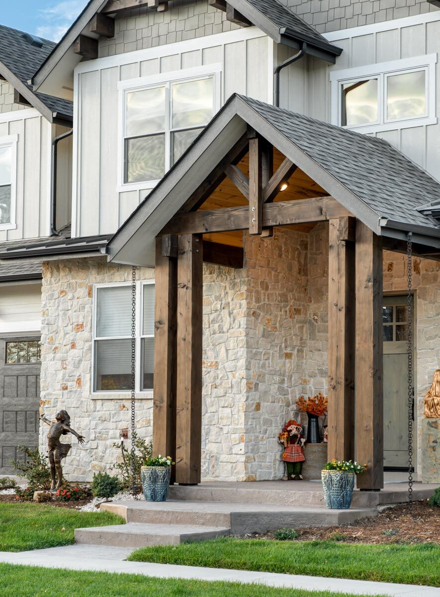 A concrete stoop complements the entry porch framed with rustic beams.