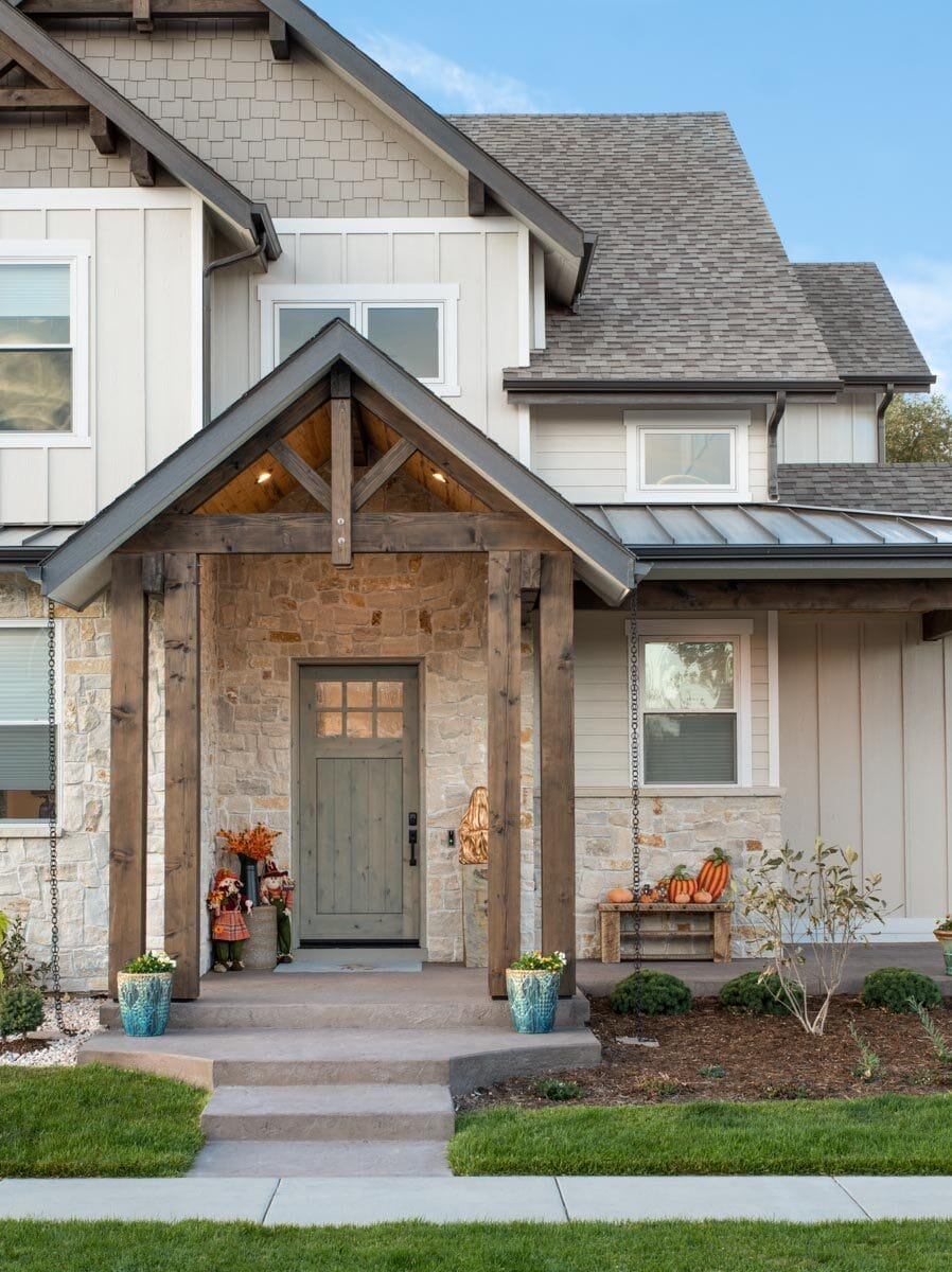 The entry porch includes a wooden front door highlighted by stone exterior walls.