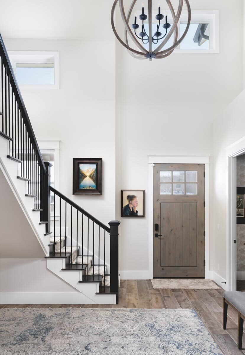 Foyer with a wooden staircase and a spherical chandelier that hangs from the two-story ceiling.