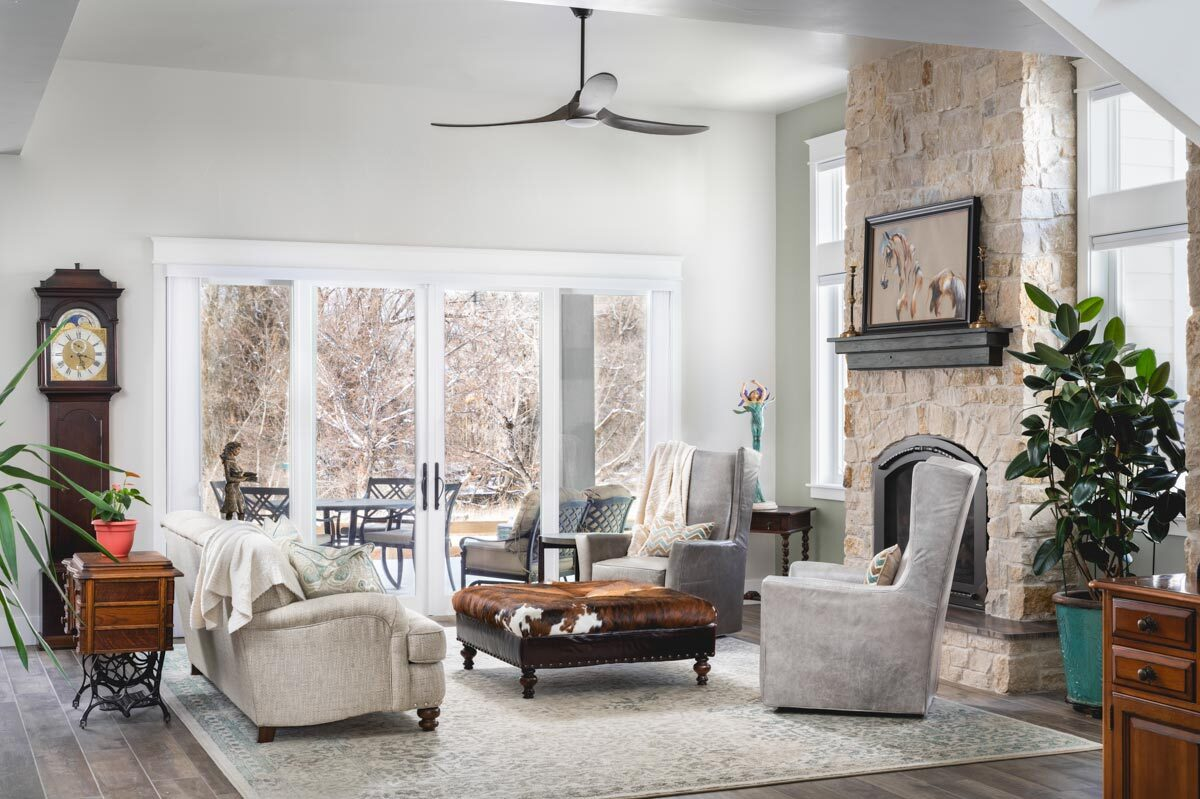 Living room with a stone fireplace, a beige sofa, and gray wingback chairs surrounding the leather ottoman.