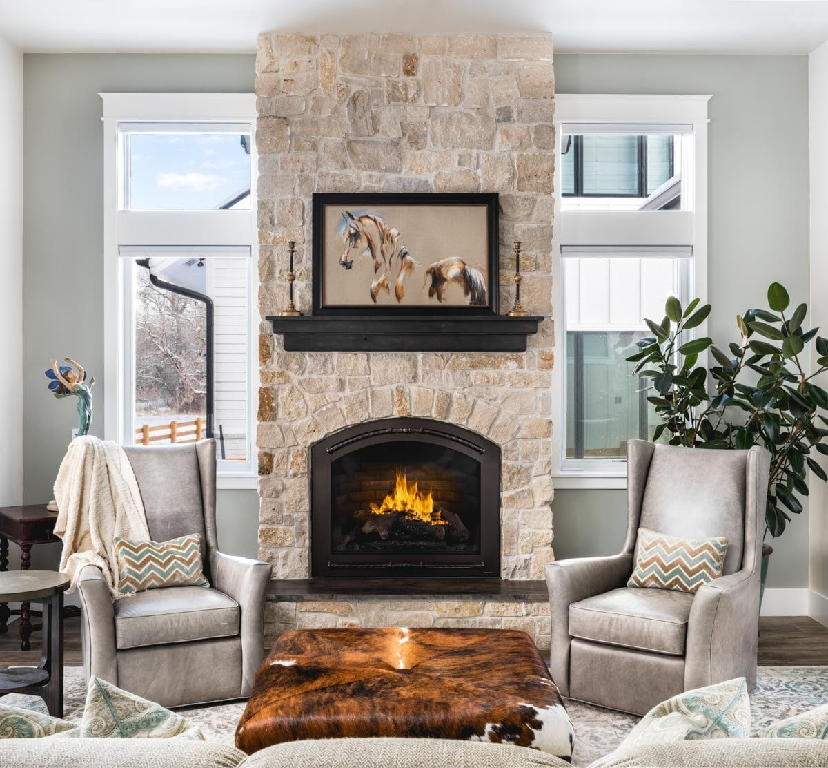 White framed windows flank the stone fireplace. A potted plant on the side emits a refreshing ambiance.