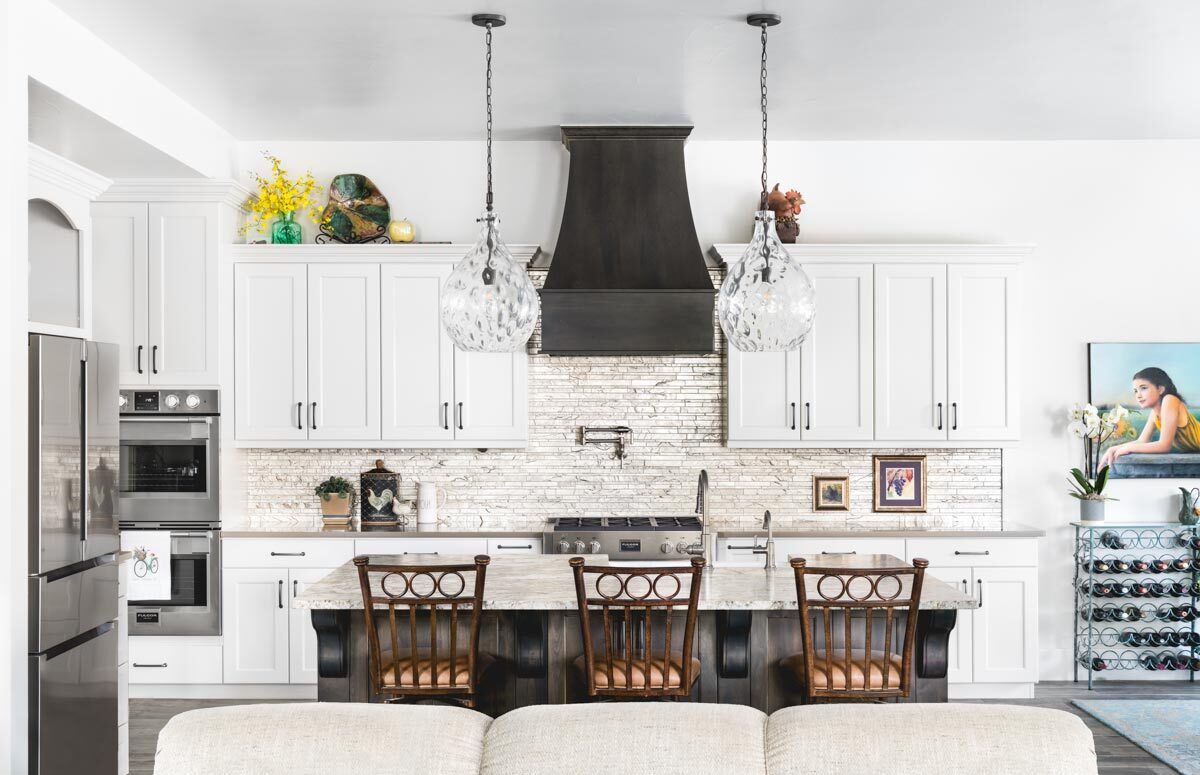 The kitchen is equipped with stainless steel appliances, a standalone wine rack, white cabinetry, and a breakfast island.