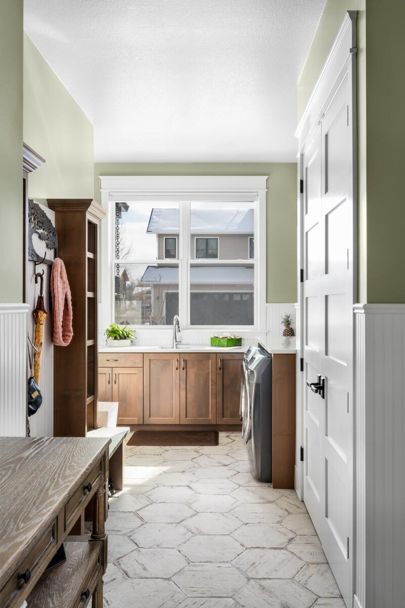 Laundry room with wooden cabinets, front-load appliances, a sink, and a large window that brings natural light in.