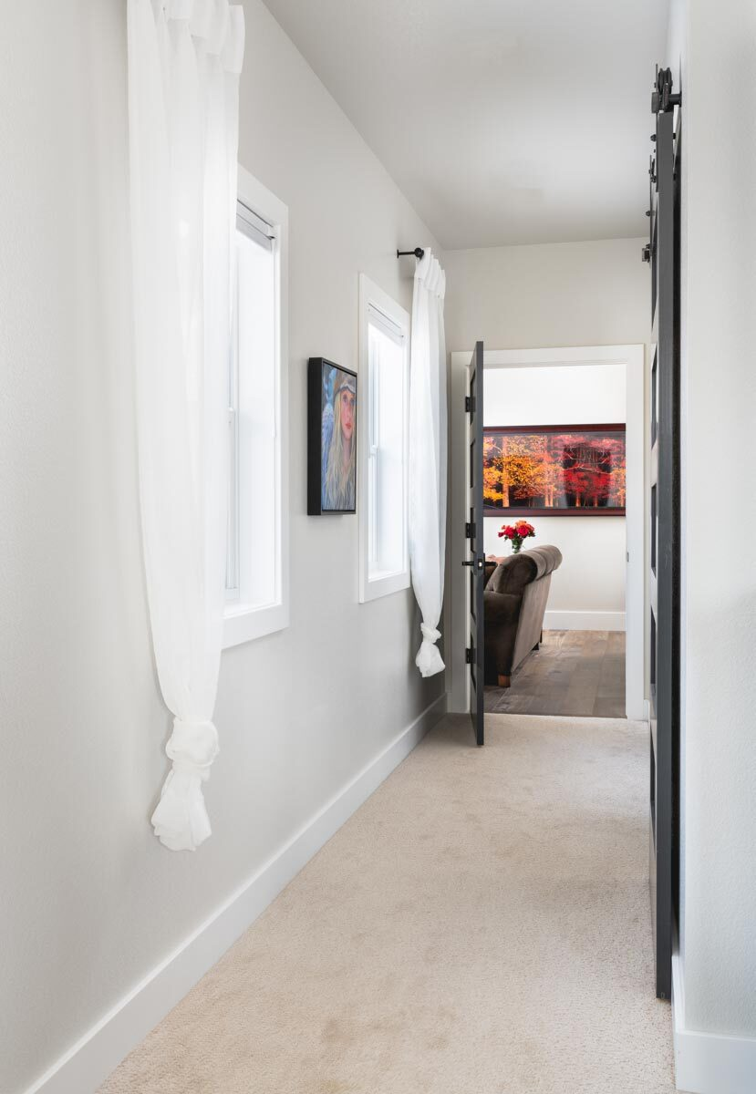 Hallway with carpet flooring, gray walls, and white framed windows graced with a lovely artwork.