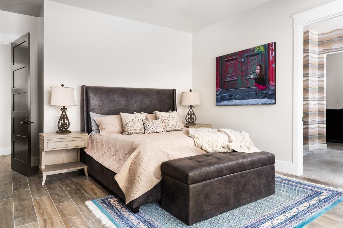 The primary bedroom features light wood nightstands and a leather bed with matching storage bench.The primary bedroom features light wood nightstands and a leather bed with matching storage bench.