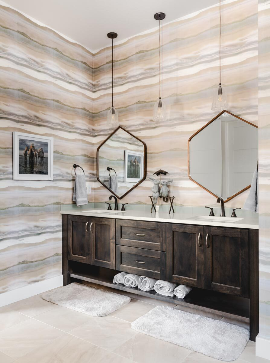 Primary bathroom with a dark wood vanity equipped with double sinks and hexagonal mirrors.