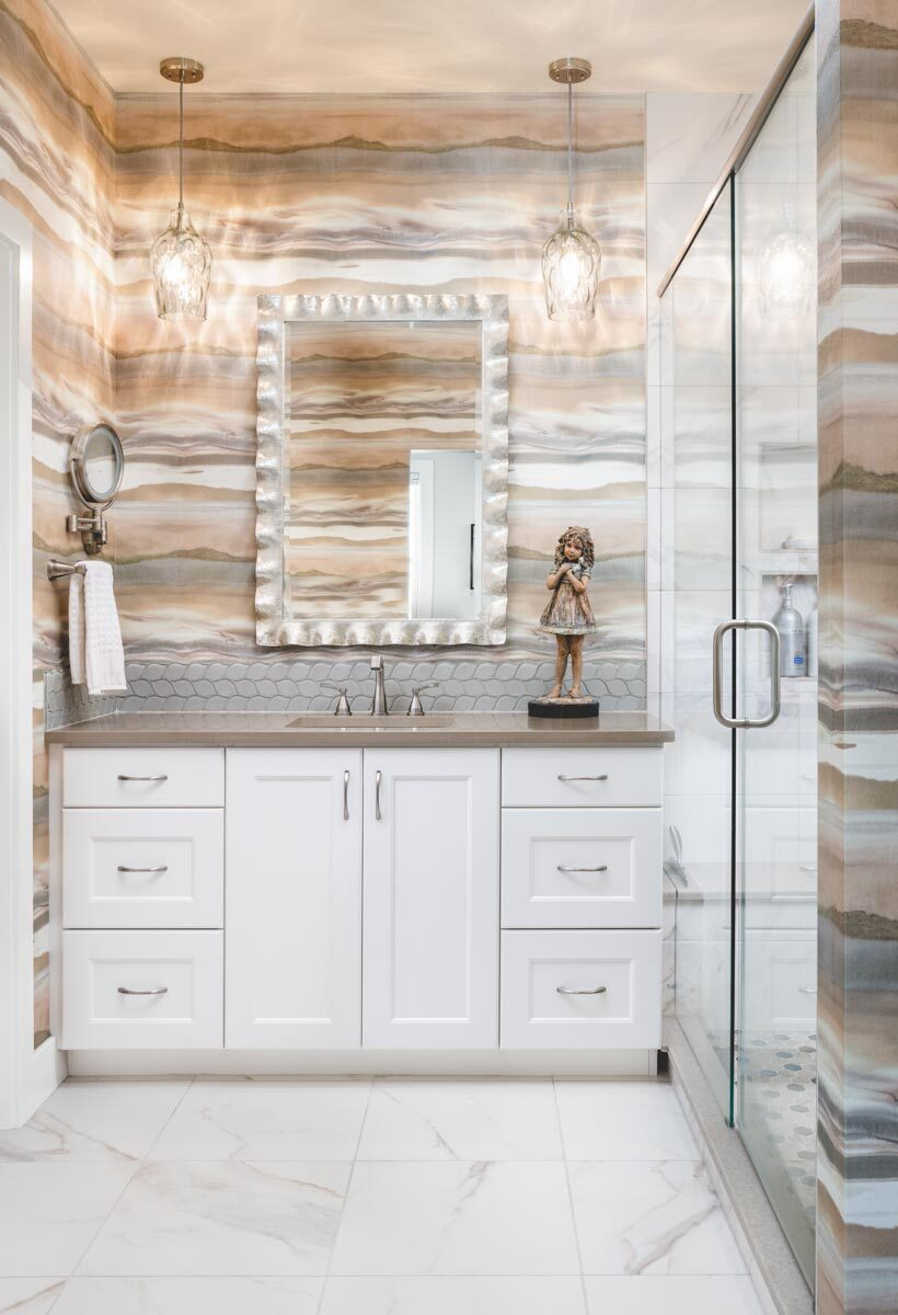 This bathroom offers a sink vanity and a walk-in shower enclosed in a glass hinged door.
