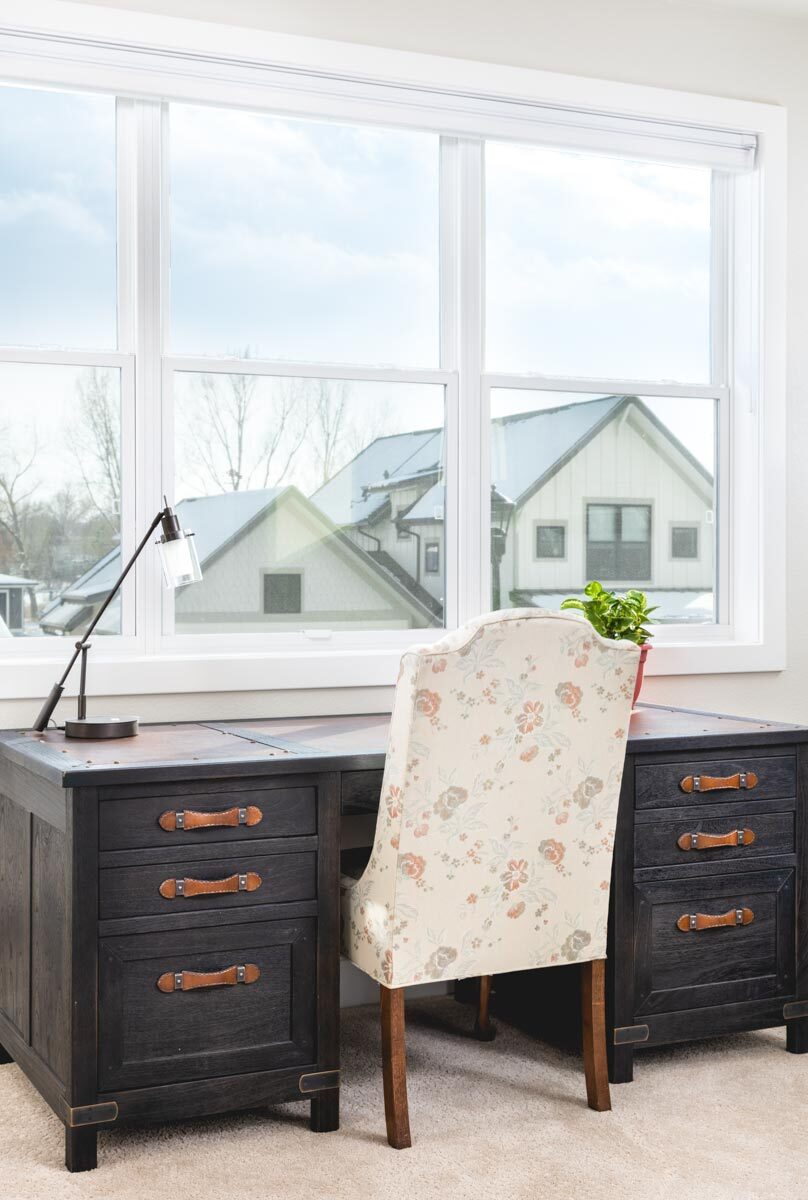 Study with a dark wood desk and a floral chair over carpet flooring.