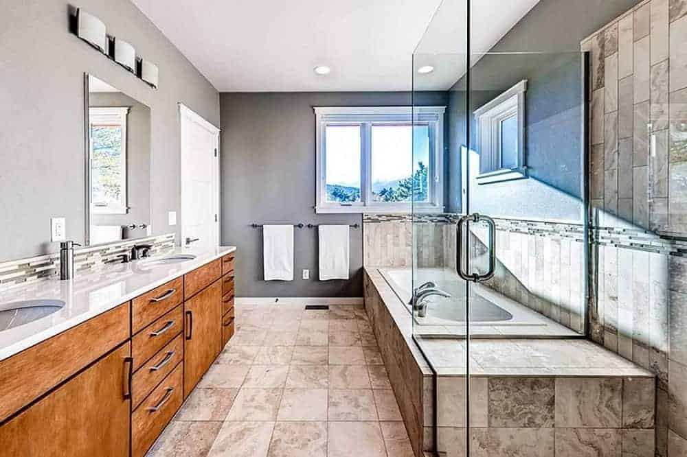 This is a long and narrow bathroom with a long two-sink vanity on one side and a bathtub across beside the glass-enclosed shower area apposite from the window.