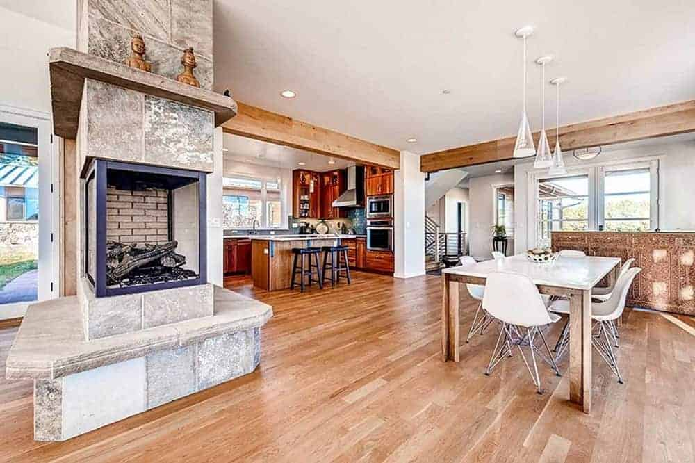 A few steps from the kitchen and living room is the dining area that has a large hardwood flooring area that makes the white dining set stand out with matching white pendant lights hanging from the white ceiling.