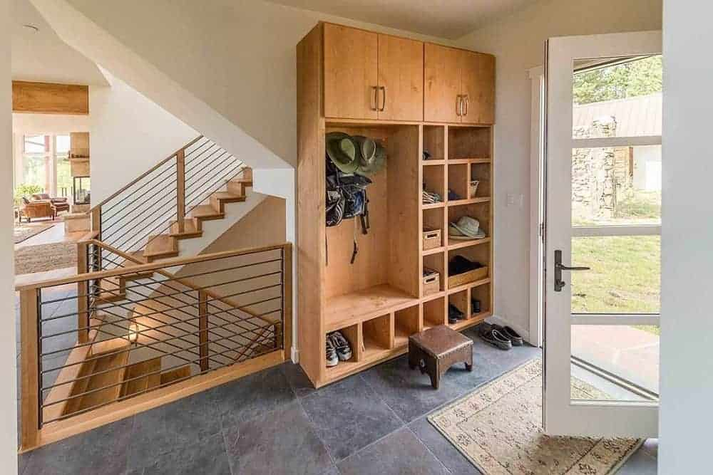This is a cozy little foyer with a wooden mudroom that has built-in shelves, cabinets and coat rack by the glass doors that bring in natural lighting.
