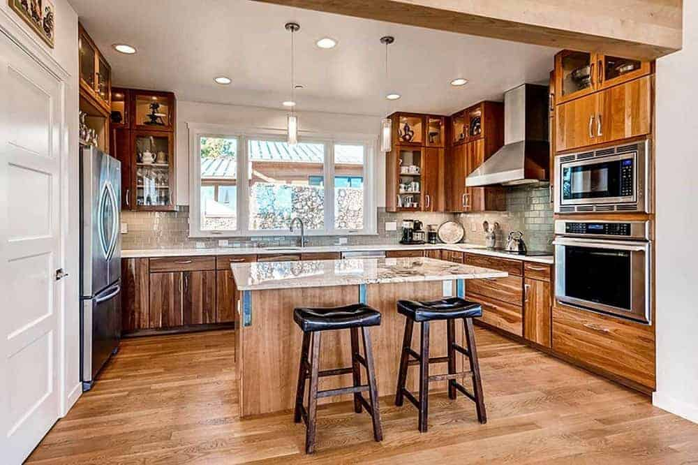 This is a close look at the kitchen that has brown wooden cabinetry lining the walls that match well with the hardwood flooring and small wooden kitchen island in the middle paired with a couple of black backless stools.