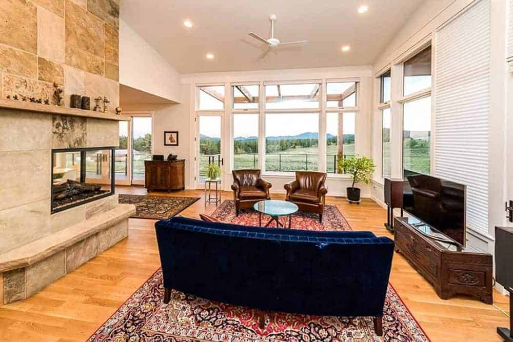 This is a close look at the living room that has a hardwood flooring, patterned area rugs, a blue velvet sofa and a large modern corner fireplace across from the TV.