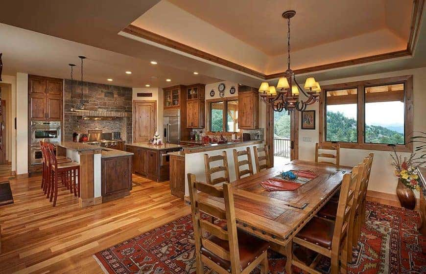 This is a look at the eat-in kitchen that has a wooden dining set next to the wooden cabinetry of the kitchen that has a coupleo f islands, a peninsula and a cooking area with mosaic stone backsplash.
