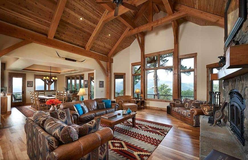 This is a full view of the living room that has a tall wooden arched ceiling with exposed beams as well as a stone fireplace across from the brown leather sofa set complemented by a patterned area rug.