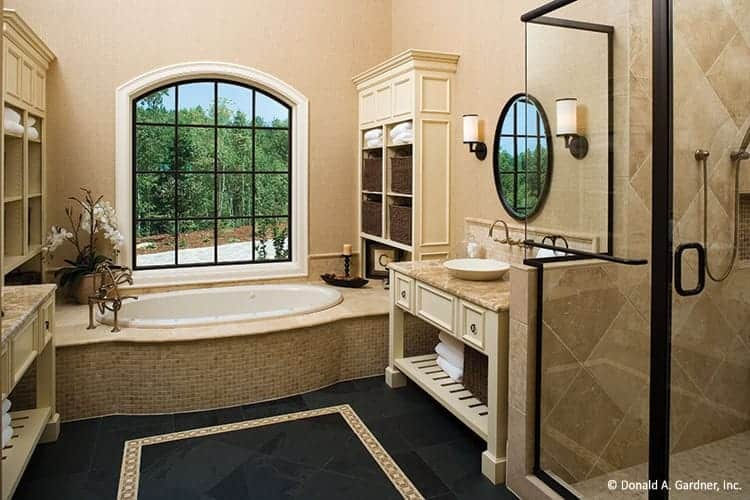 This is a close look at the primary bathroom that has a glass-enclosed shower area next to the simple vanity with beige drawers. The bathtub is housed on the far side under the window.