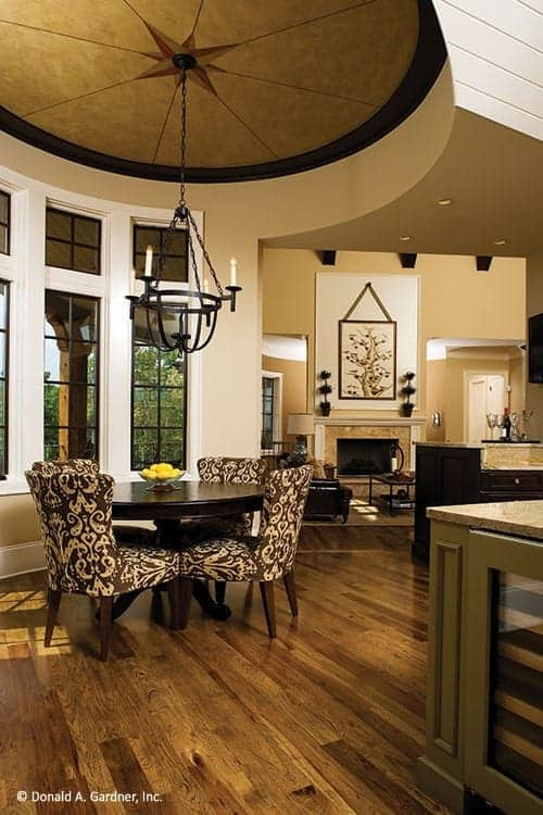 A few steps from the kitchen is the dining area with a dark wooden round table surrounded by patterned dining chairs under a cove ceiling that hangs a simple chandelier over the table.