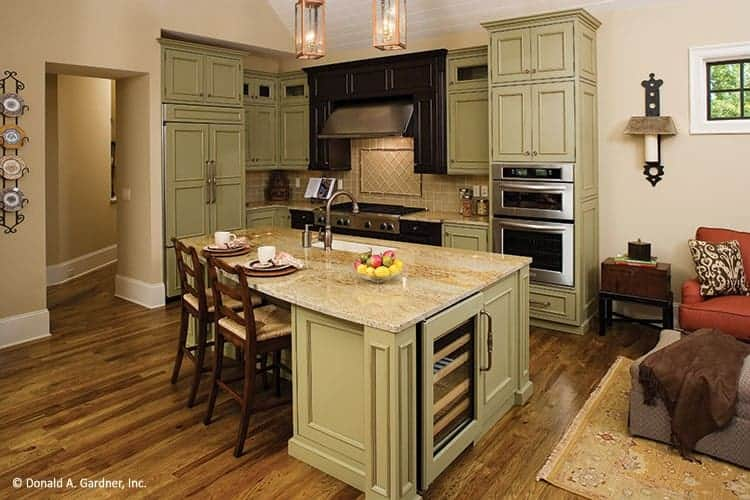 This is a close look at the mountain-style kitchen that has light green shaker cabinets that match the kitchen island and contrast the stainless steel appliances.