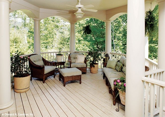 Covered porch with cushioned wicker seats surrounded by decorative archways.