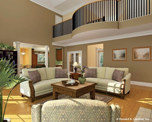 Living room with beige sofas and a wooden coffee table that sits on a printed area rug.