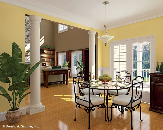 Breakfast room with a round glass top dining table and ornate iron chairs over the hardwood flooring.