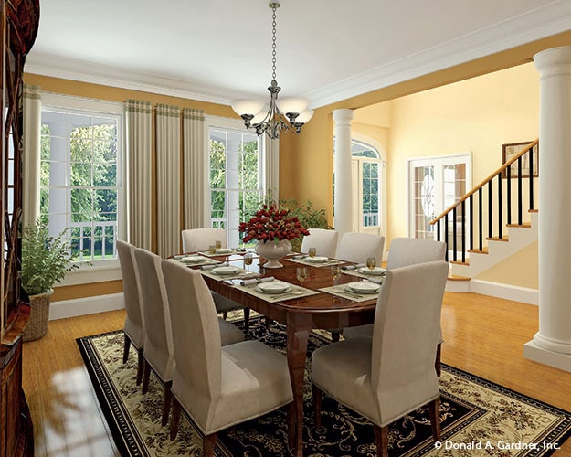 Formal dining room with beige upholstered chairs, an oval dining table, and a glass chandelier.
