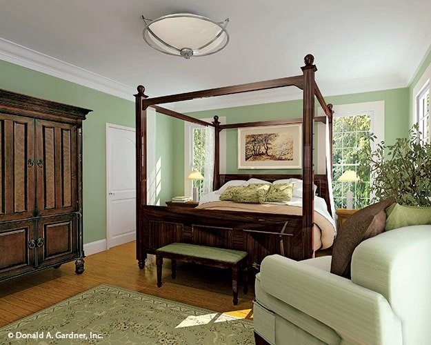Primary bedroom with a comfy armchair and a canopy bed that matches with the wooden wardrobe.