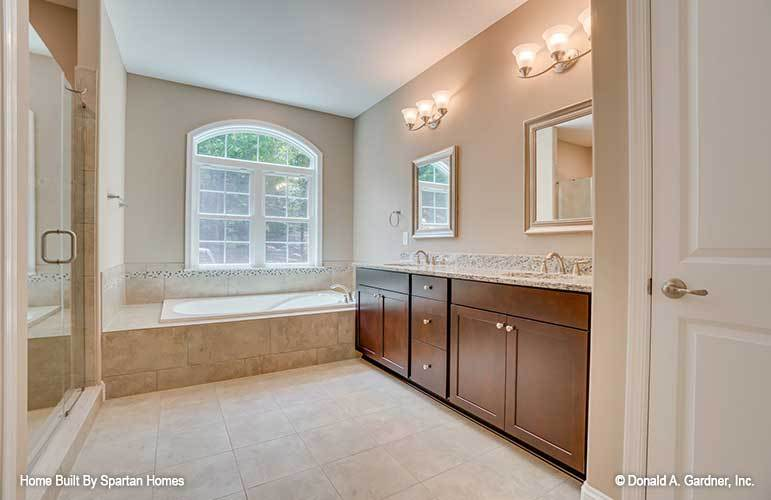 This is a simple yet luxurious primary bathroom with a large dark wooden two-sink vanity topped with wall mirrors and sconces next to the bathtub under the window and across from the glass-enclosed shower area.