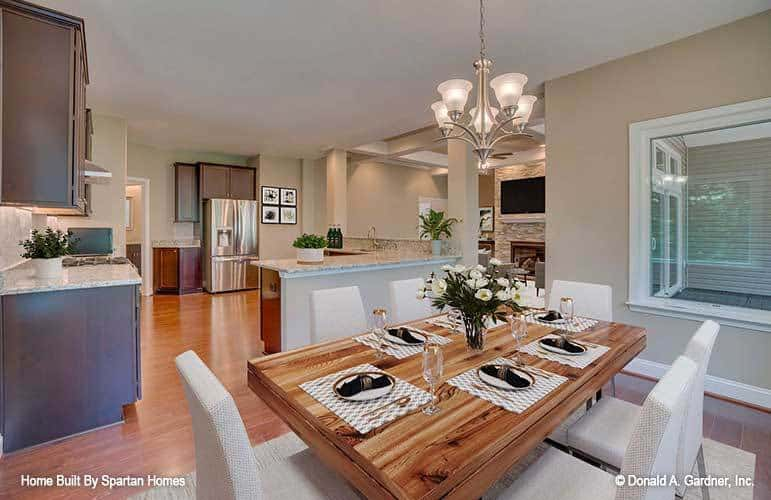 This is a close look at the dining area with a rectangular wooden dining table topped with a simple chandelier and surrounded by cushioned chairs that stand out against the hardwood flooring.
