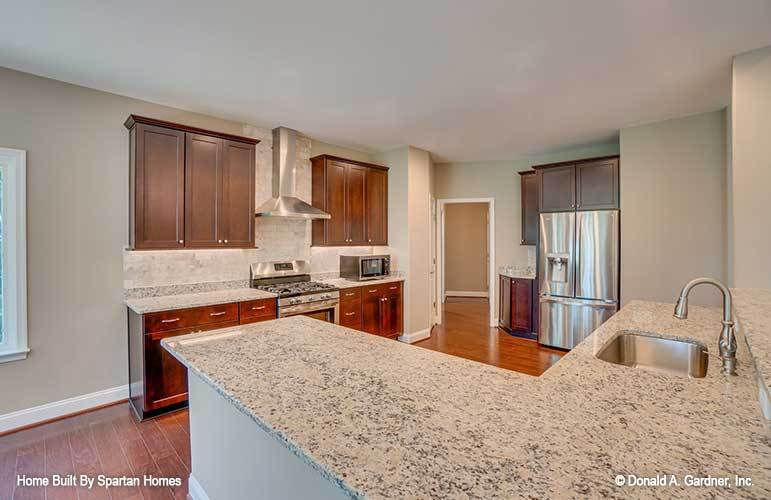This is the kitchen that has wooden cabinetry lining the walls as well as stainless steel appliances that stand out against the hardwood flooring. The kitchen also has an L-shaped peninsula across from the cooking area.