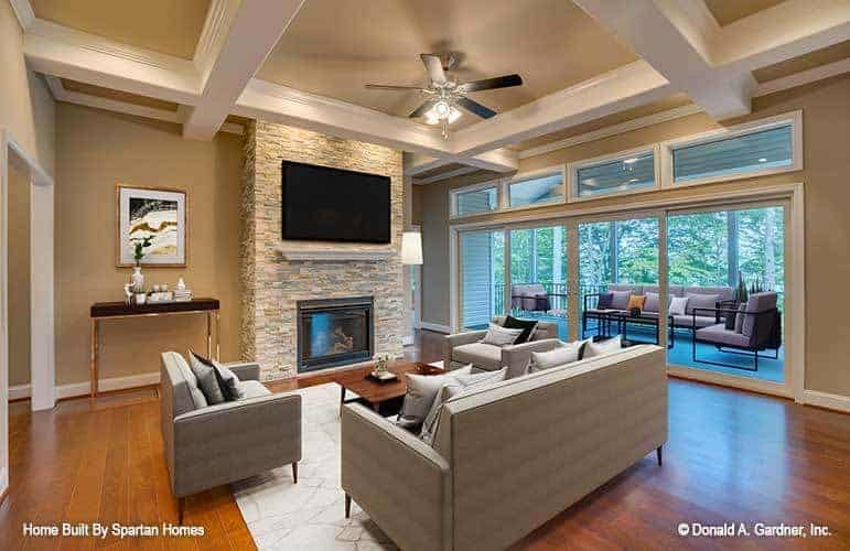 The spacious living room has a modern gray sofa set and a dark wooden coffee table that matches the hardwood flooring. These are then complemented by the large gray brick fireplace with a wall-mounted TV above it.