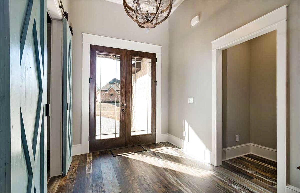 The foyer has a french entry door, a spherical chandelier, and hardwood flooring.
